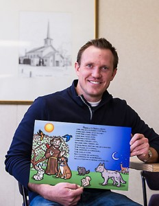 Tom Wall with an illustration of St. Francis of Assisi and the Prayer of St. Francis. He made the poster as a Christmas gift for his niece and nephews and now plans to create a Catholic children's book of prayers.  Photo credit: Sam Lucero, The Compass